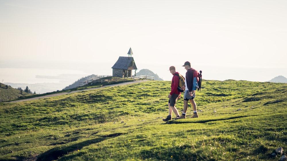 two man walking on mountain during daytime