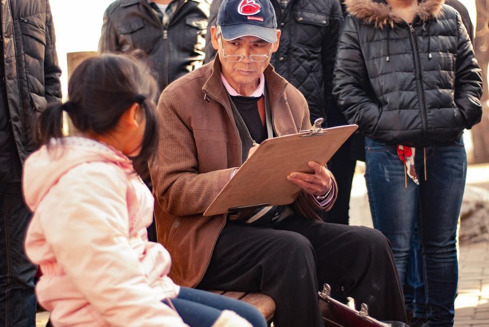man sitting beside sitting girl in pink hoodie