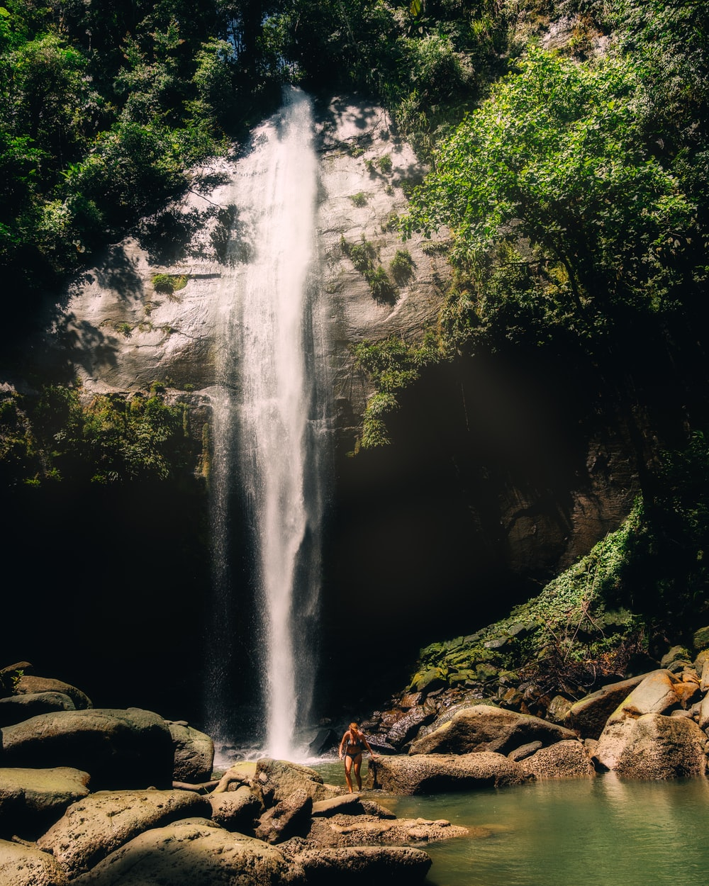 person standing on brown rock near waterfalls surrounded with green trees during daytime