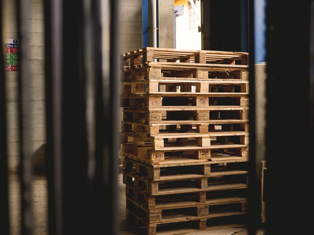 selective focus photography of piled brown wooden pallets