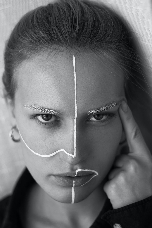grayscale photography of woman wearing earring touching eyebrow