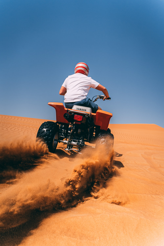 person riding ATV on desert during daytime