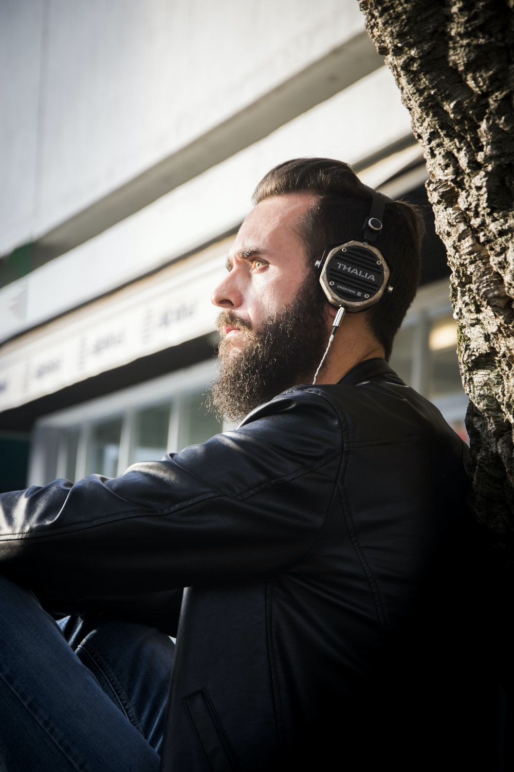 man in black leather jacket using headphones while sitting near building
