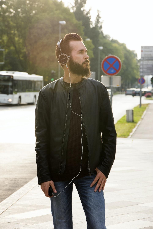 standing man wearing black corded headphones during daytime