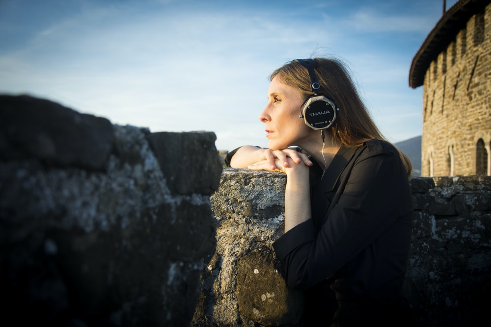 selective focus photography of woman wearing black headphones during daytime
