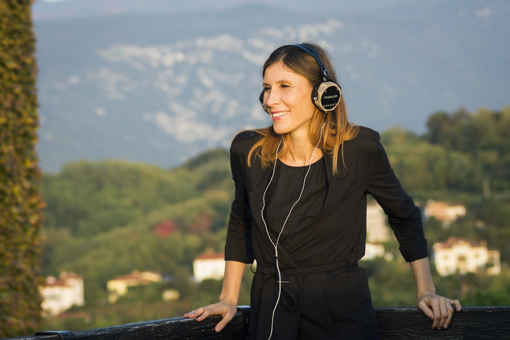 selective focus photography of smiling woman wearing black corded headphones during daytime