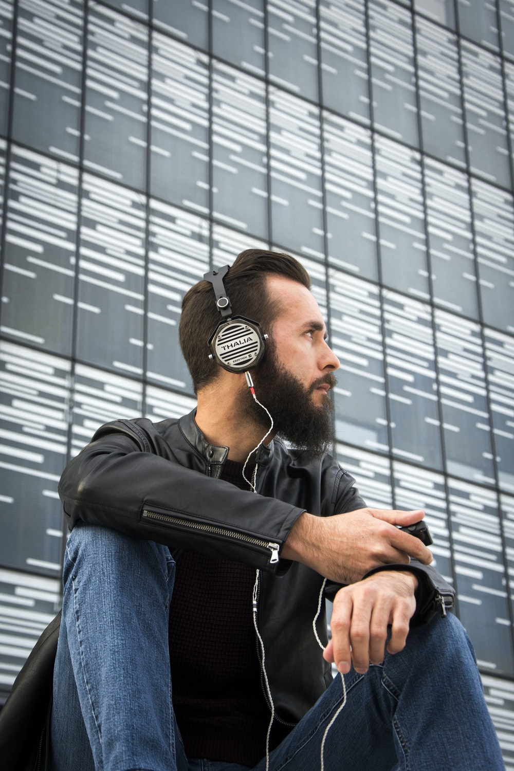 man in black leather jacket sitting while using headphones