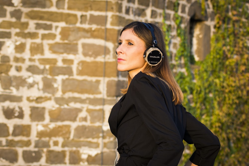 shallow focus photo of woman in black long-sleeved shirt using headphones