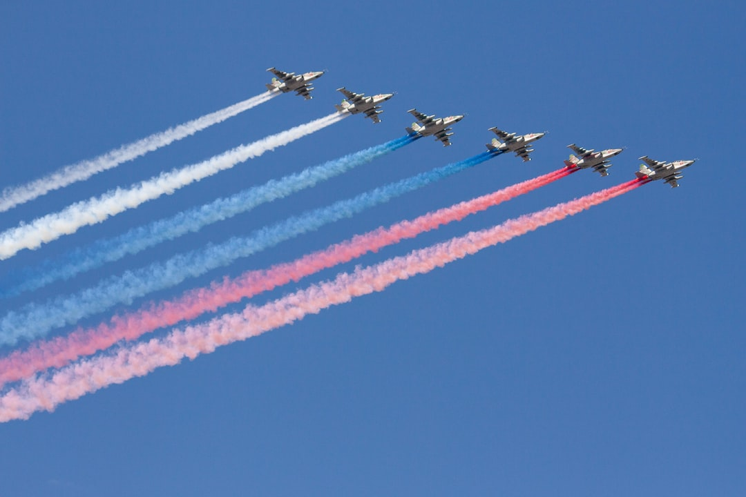 Sukhoi Su-25 assault aircrafts leave coloured trails performing at an air show.