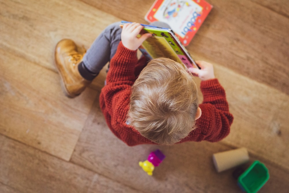 selective focus photography of sitting toddler in red sweater holding book