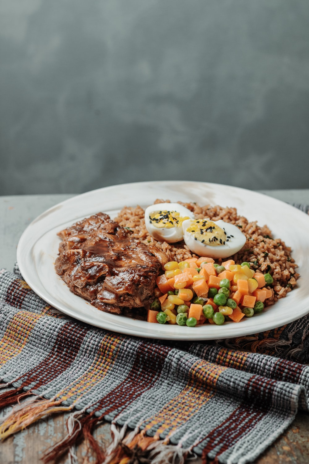 selective focus photography of meat with eggs on white plate