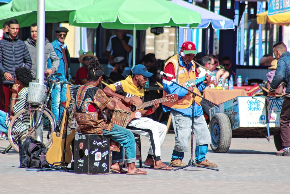 three person playing musical instrument beside green tent during daytime