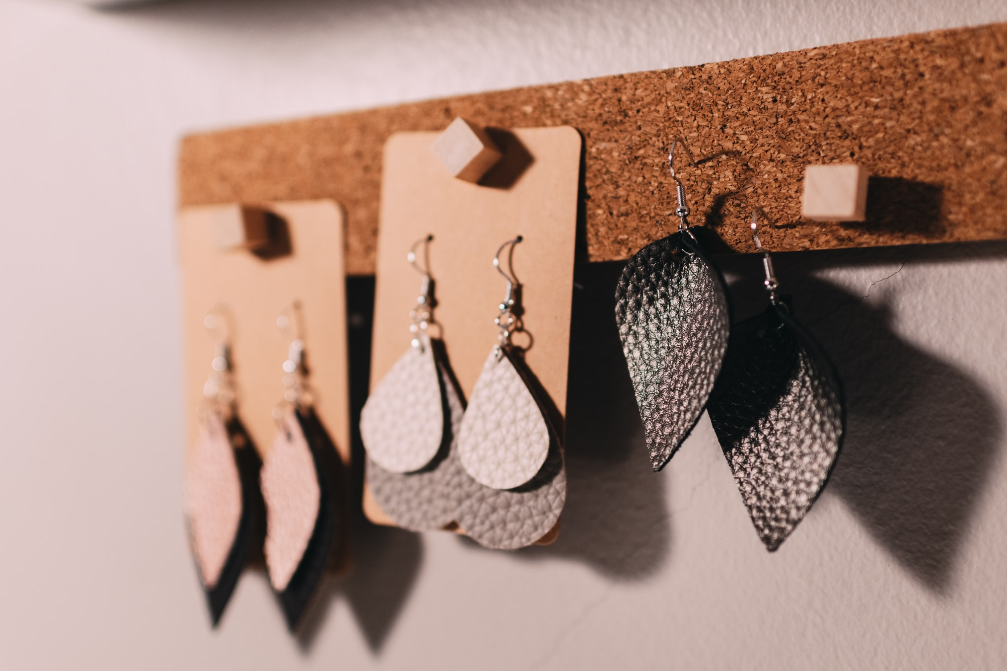 Leather earrings hanging together on a cork strip