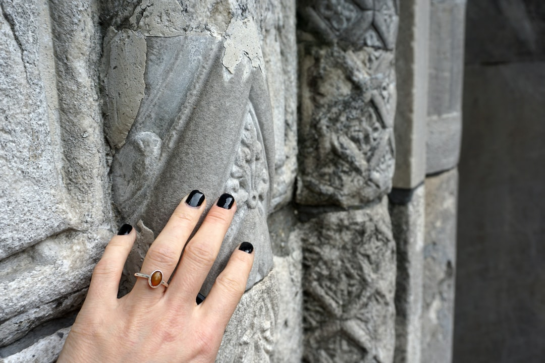 A female hand with black nails touches an old stone wall.