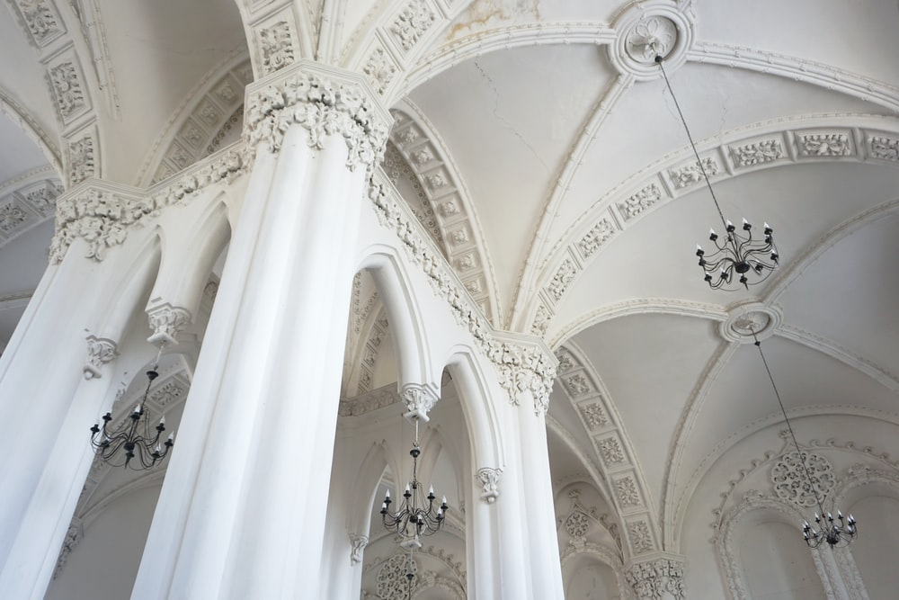 white concrete pillared building with chandeliers