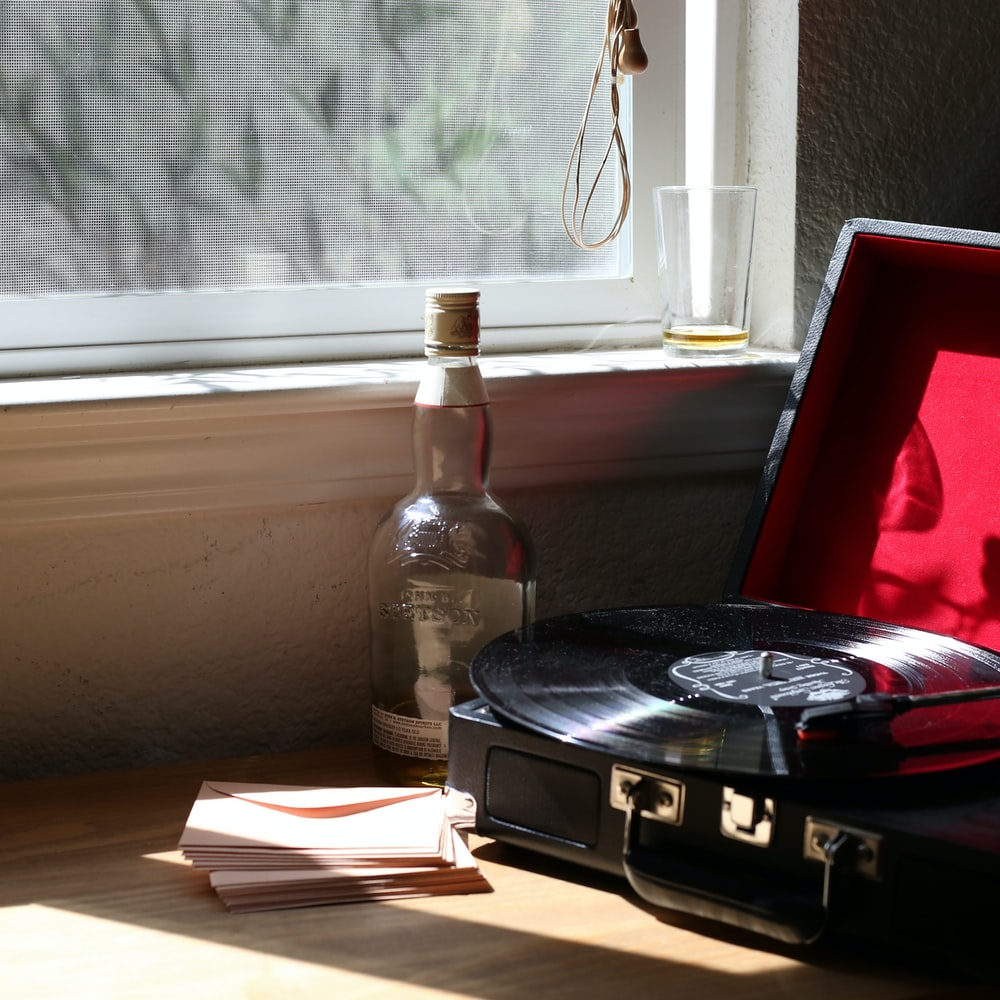 black and gray stereo turntable beside clear-glass bottle