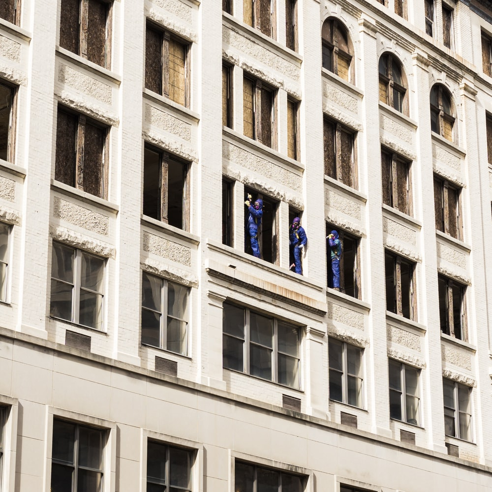 three men standing on building window panels