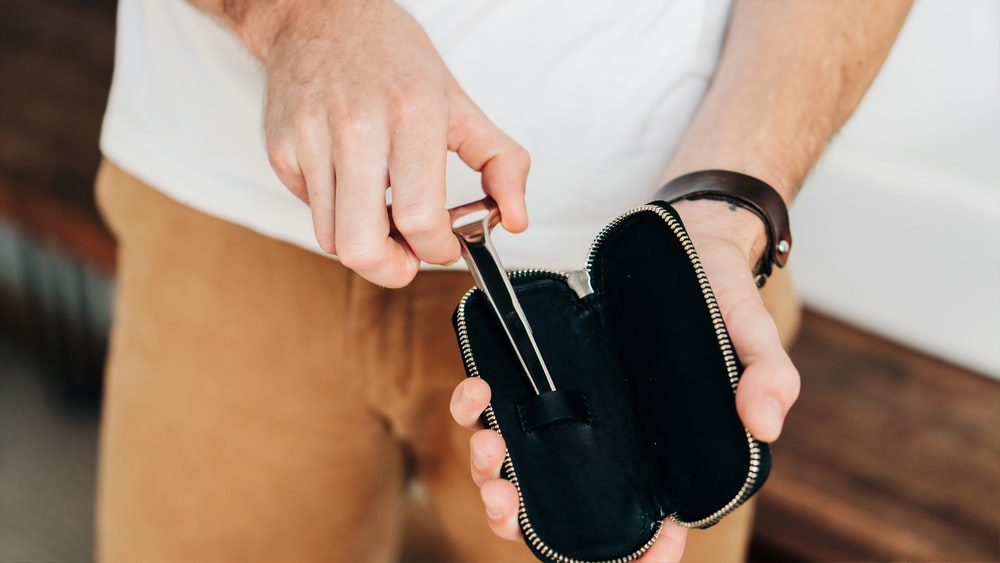 shallow focus photo of person holding black pouch bag