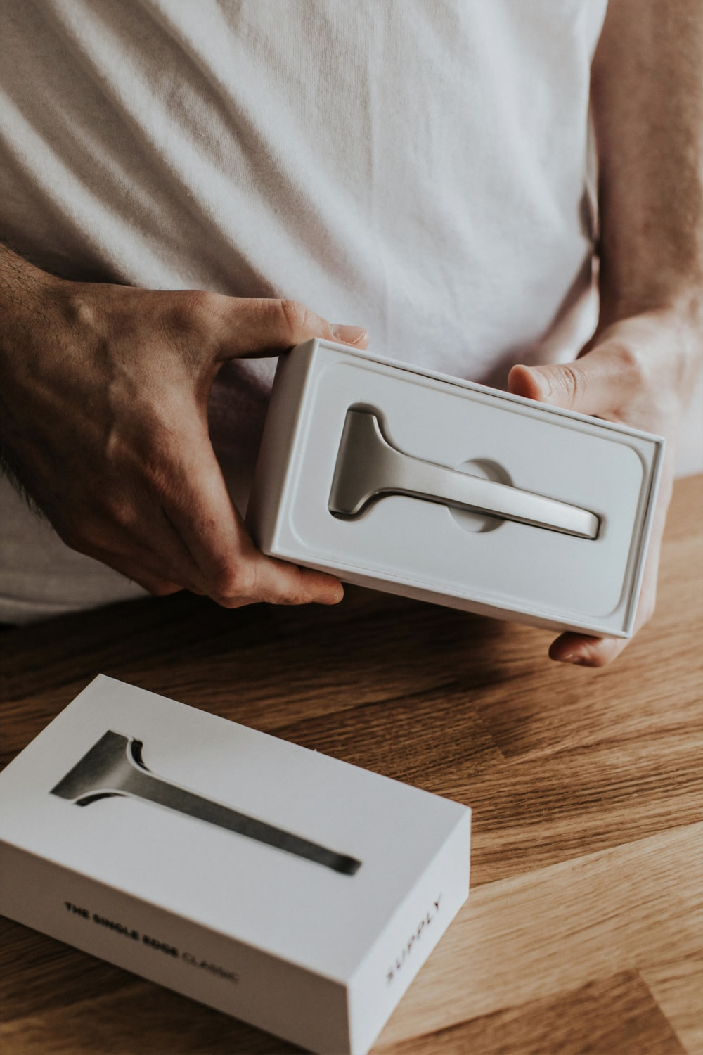 shallow focus photo of person holding gray device in white box