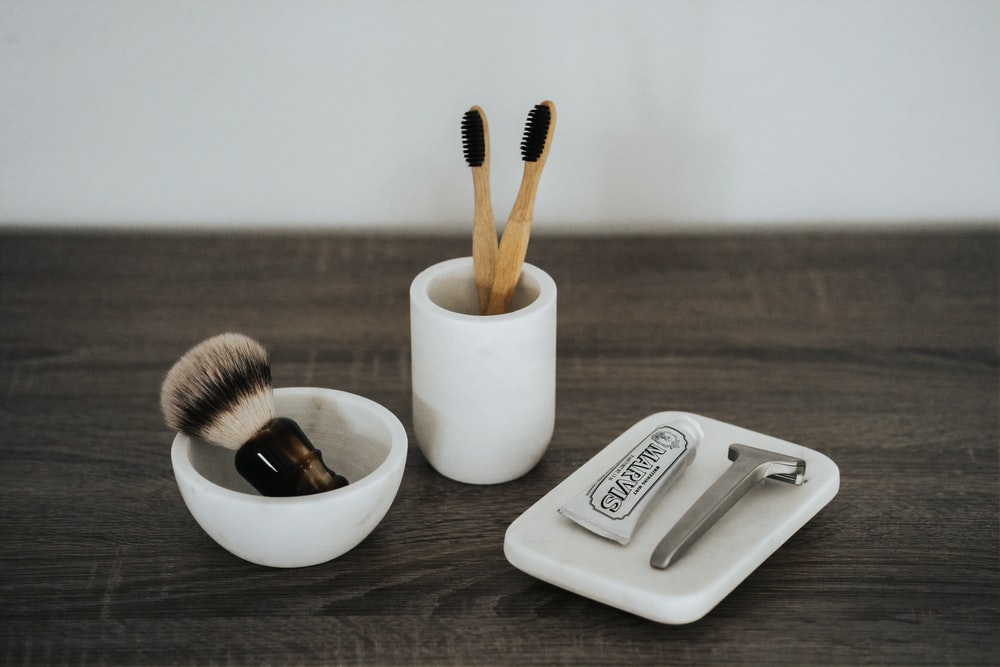 shallow focus photo of two brown brushes in white ceramic cup