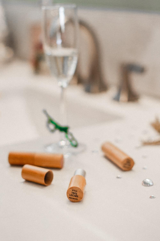 glass of white wine near lipsticks