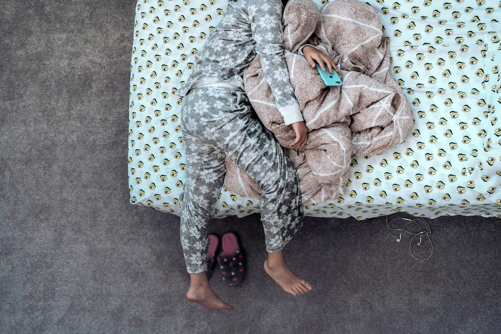 child wearing gray and white pajama lying on bed while holding phone