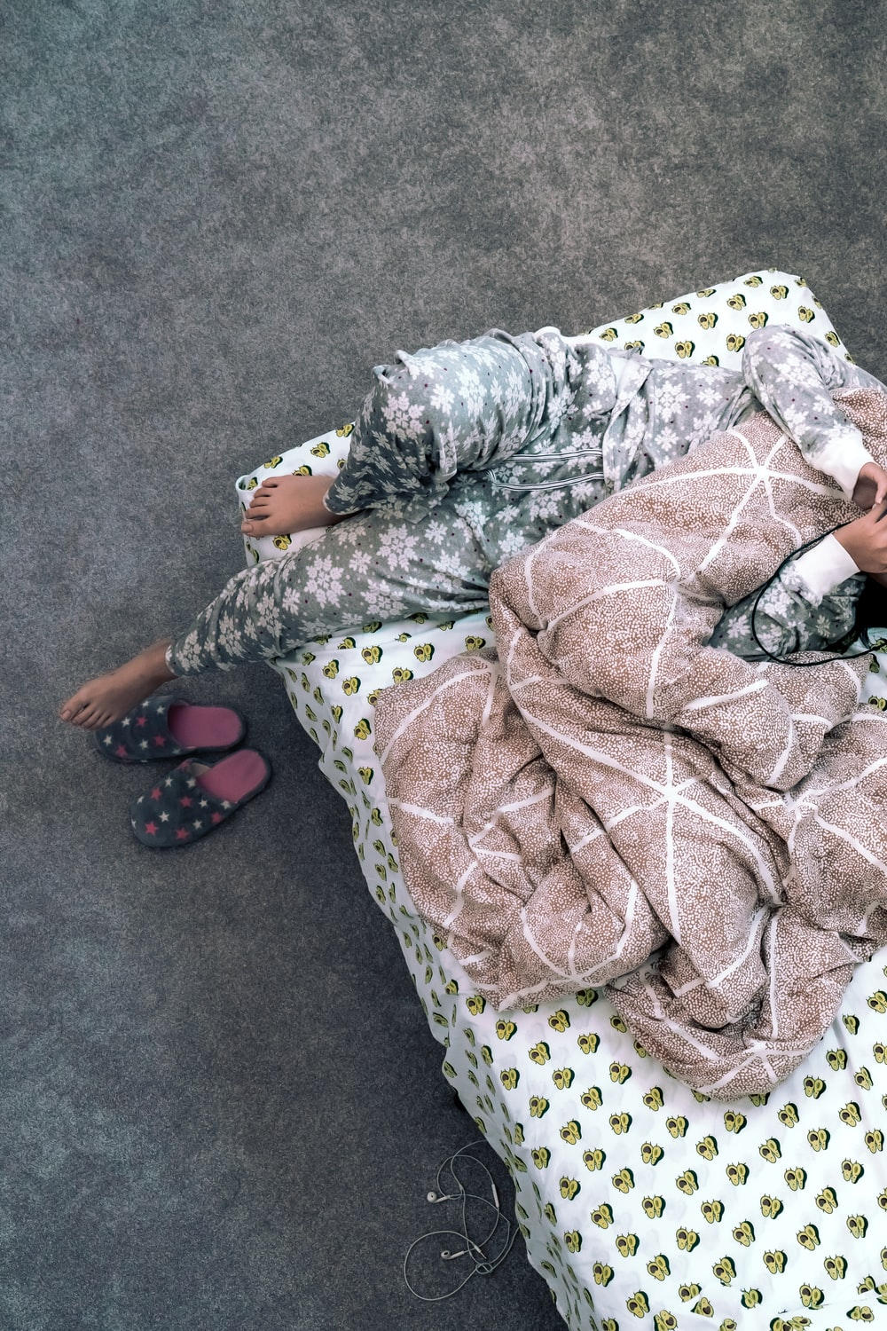 person lying in bed with gray blanket