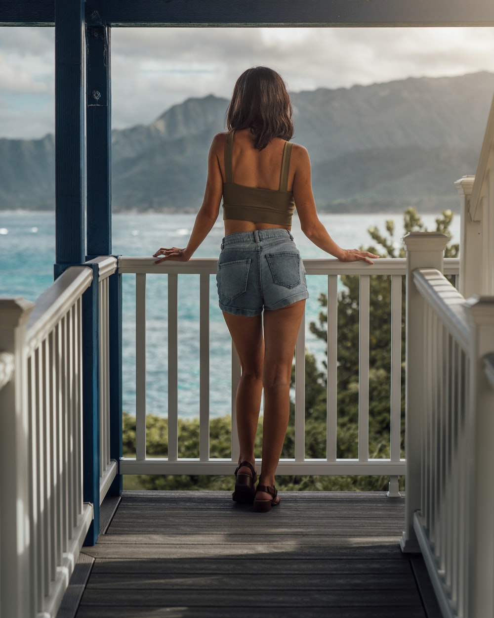 woman standing and holding handrail overlooking body of water during daytime