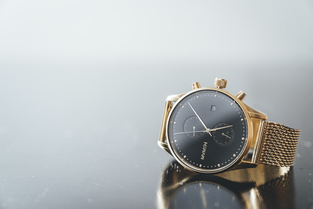 round gold-colored and black MVMTH chronograph watch with link bracelet
