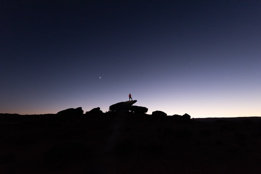 silhouette of person standing on rocks during nighttime