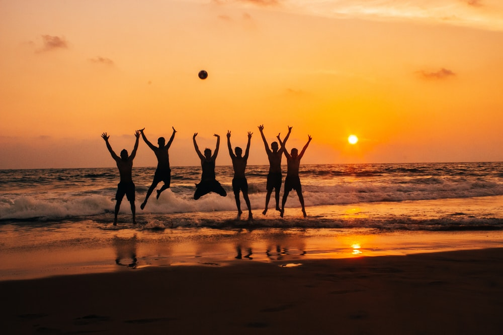 time lapse photography of group of people jumping on seashore under golden hour