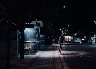man standing beside road