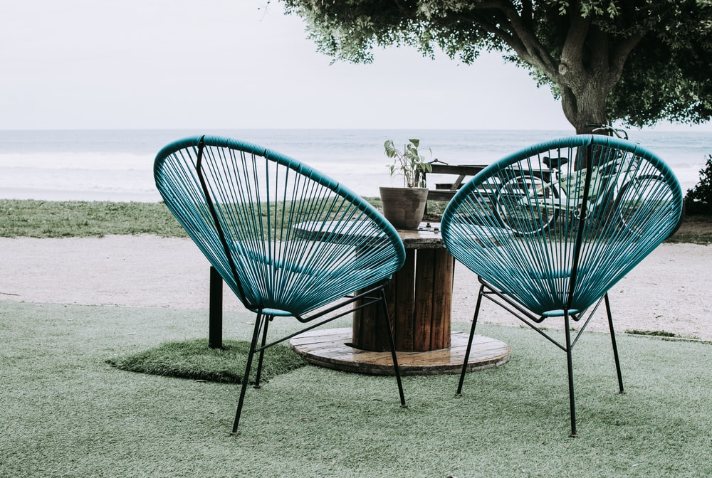 two blue chairs beside round table near ocean