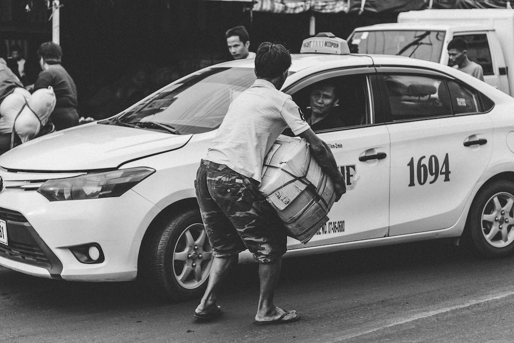 greyscale photography of man carrying cardboard box beside taxi