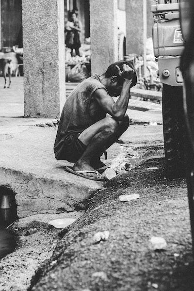 道路に座り込んで頭を抱えて落ち込んでいる男性の画像