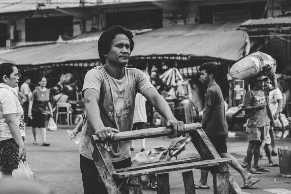 greyscale photography of man pushing cart