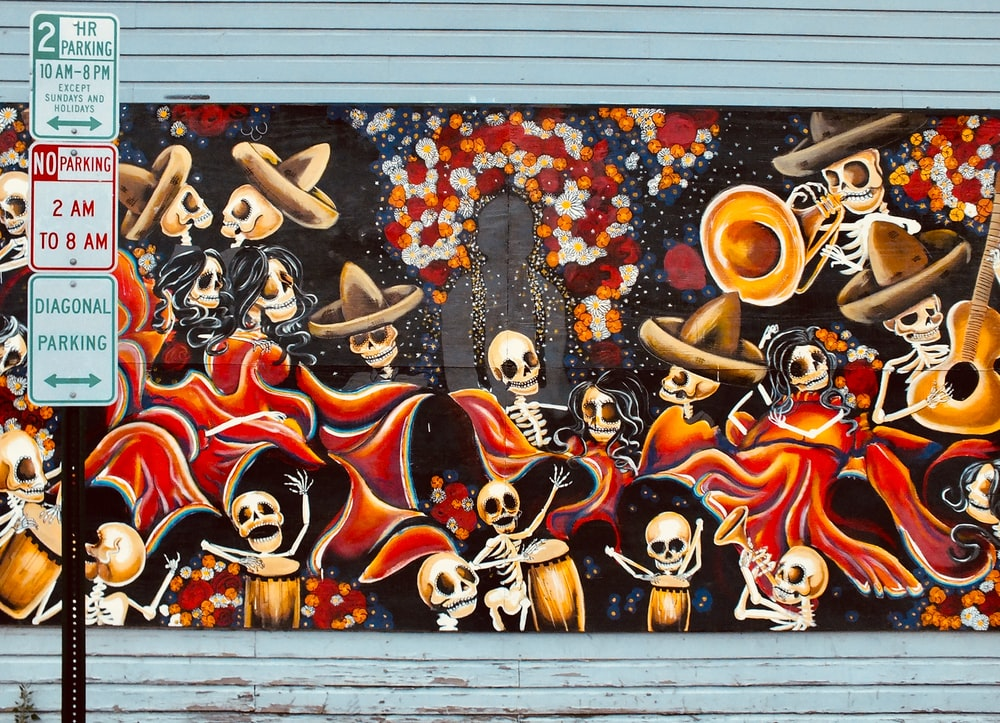 road sign in front of skeleton playing instruments graffiti