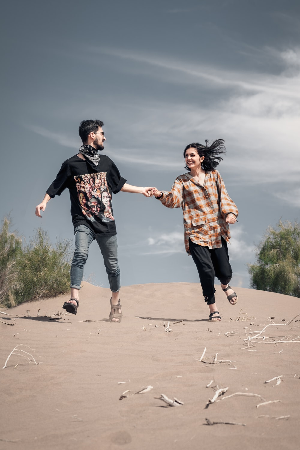 man holding hand of smiling woman walking on sand during dayitme