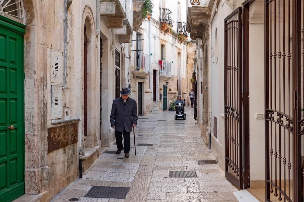 man using walking cane while walking on pathway near buildings during daytime