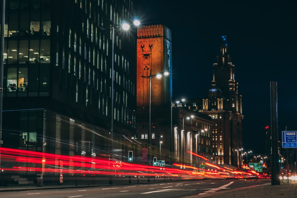 time-lapse photography of road and city with high-rise buildings during night time