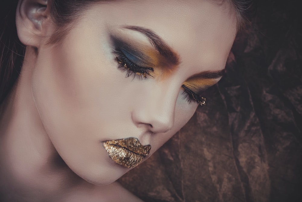 woman with gold lipstick and orange and gray eyeshadow