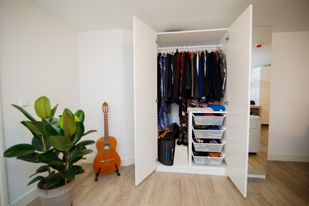 hanged assorted-colored clothes in white cabinet