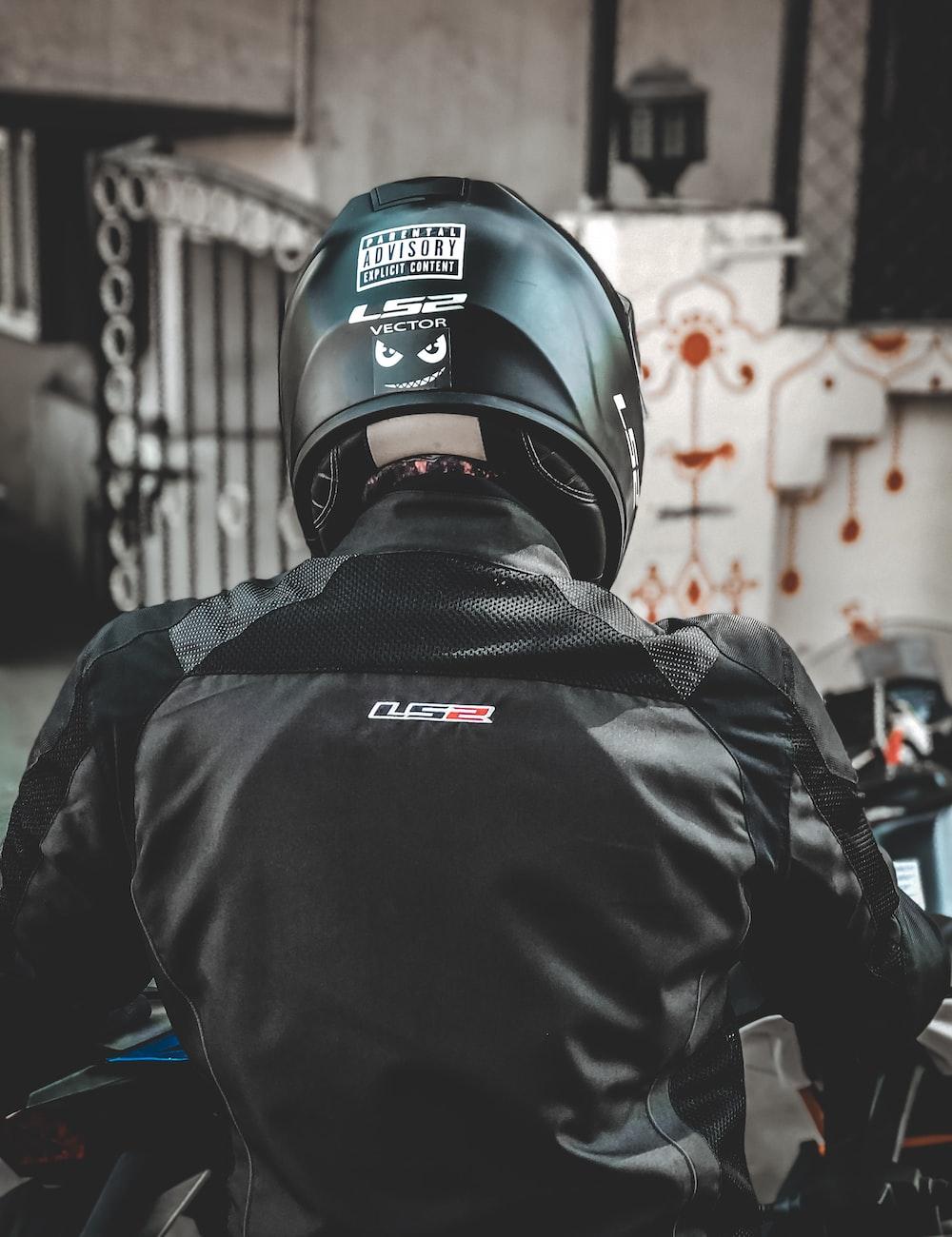 person wearing black jacket and helmet