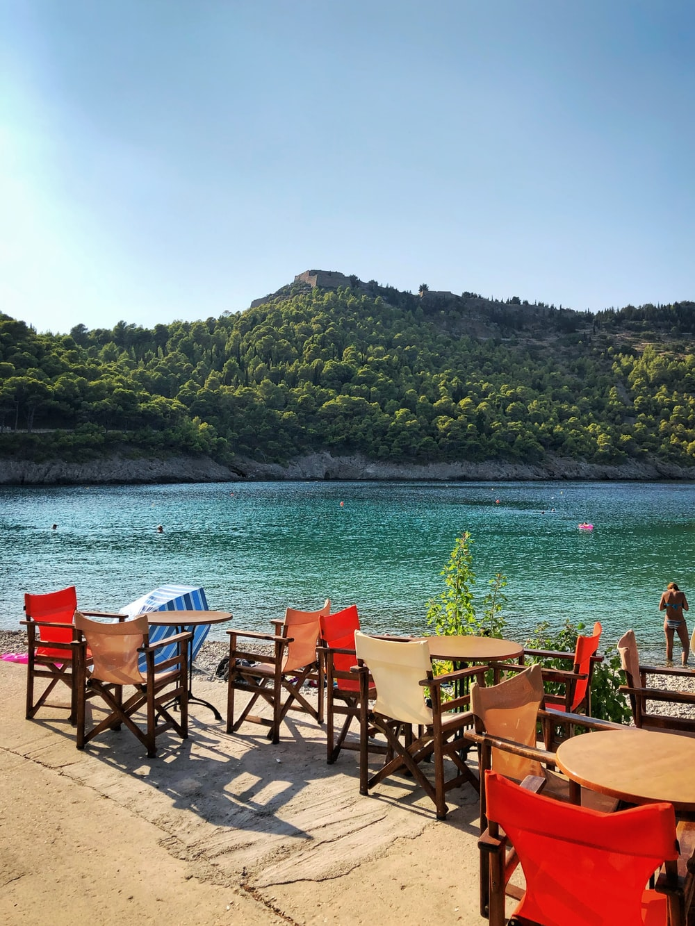 chairs and tables near body of water and mountain