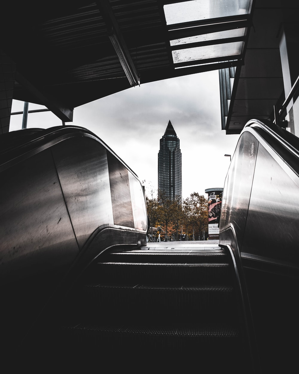 grey and black escalator with view of high-rise building
