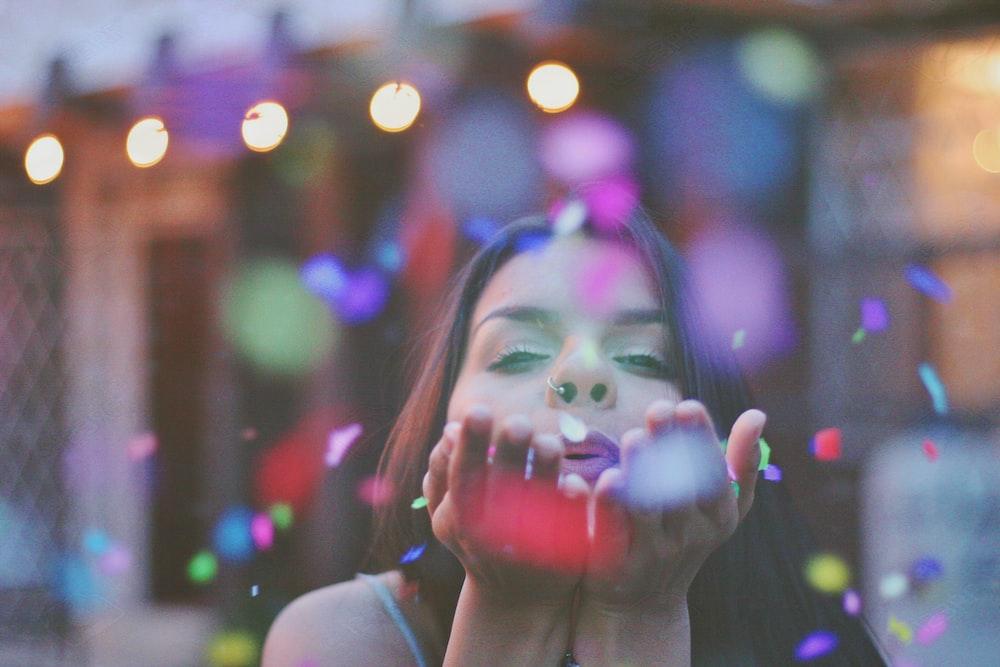 woman blowing confettis