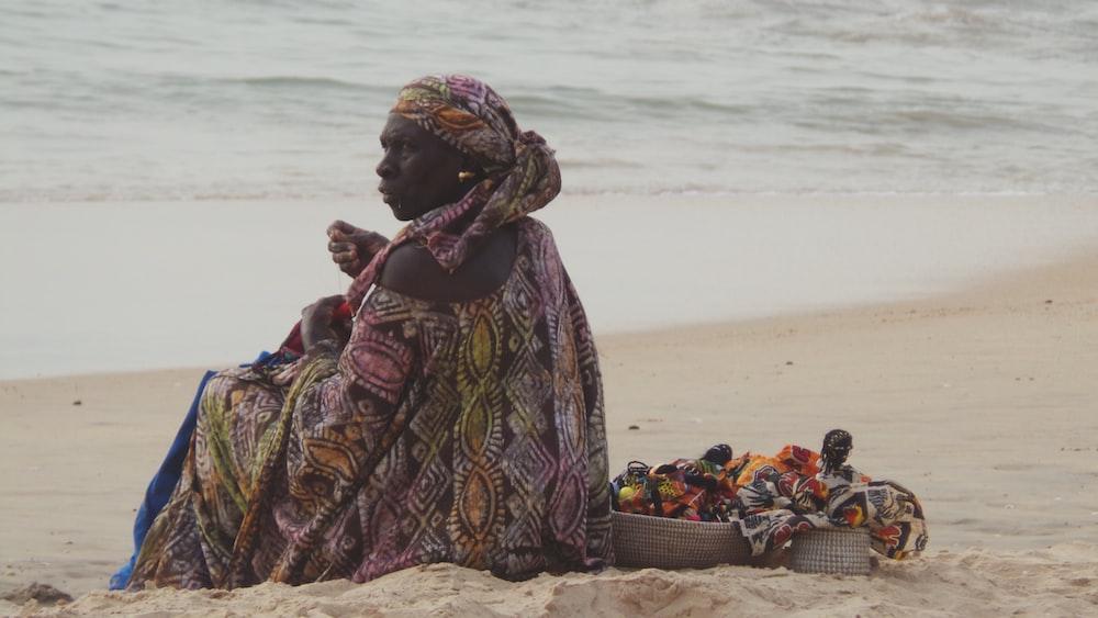 woman sitting on shore near body of water