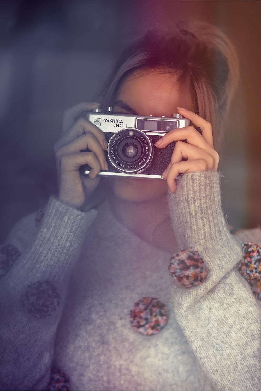 woman using silver and black DSLR camera