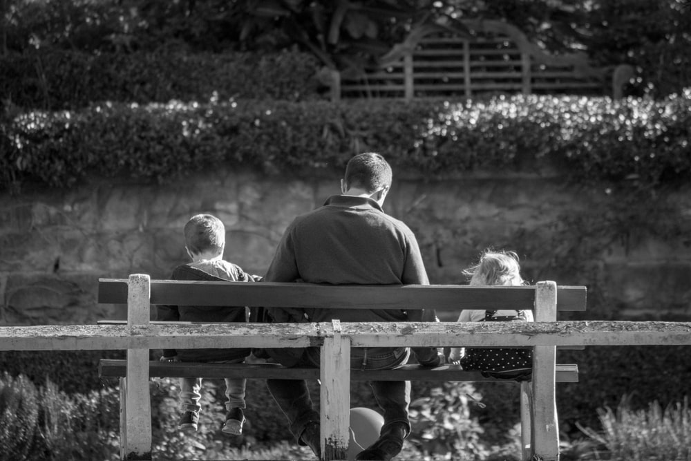 grayscale photography of man and two children sitting in bench