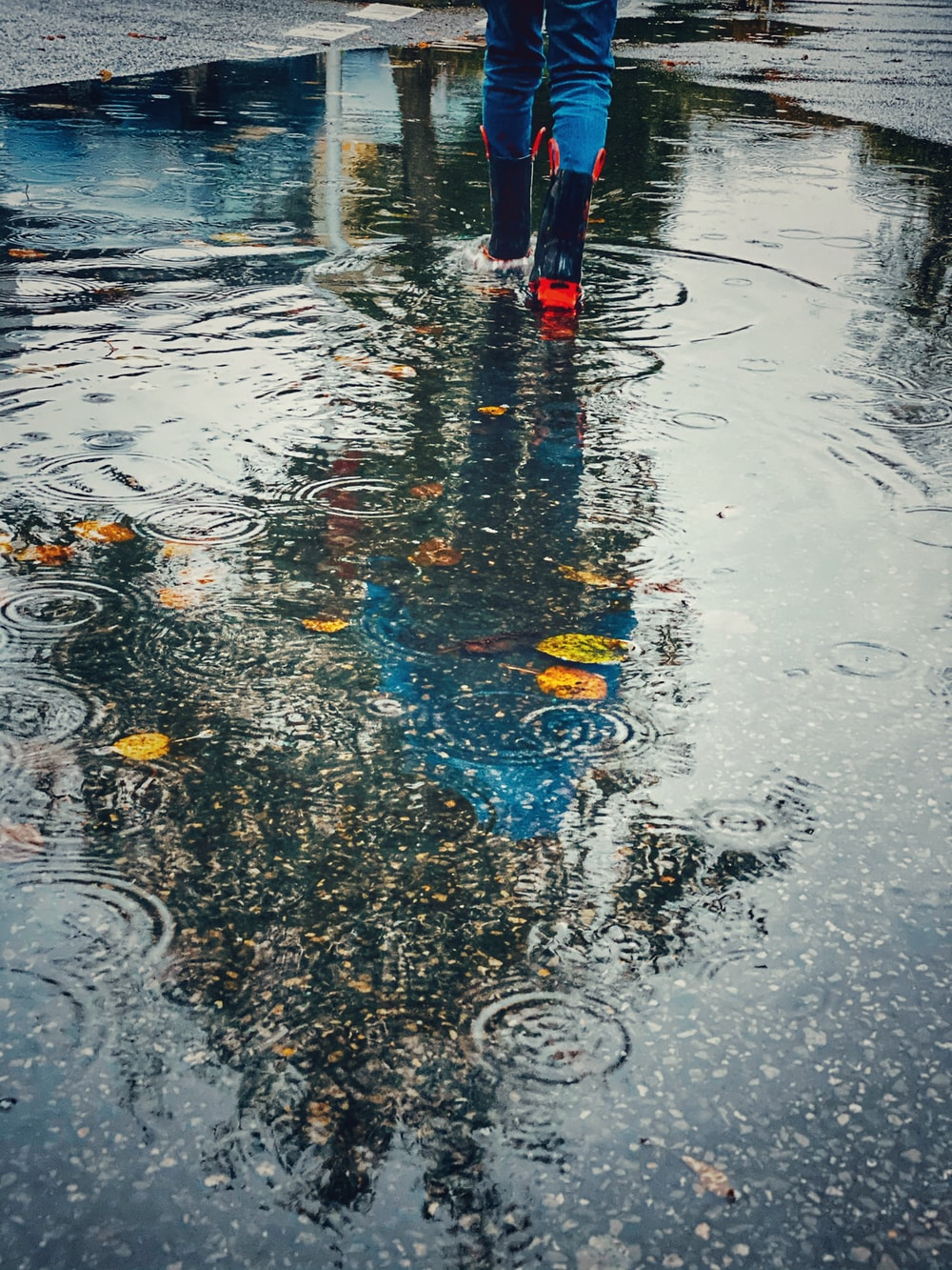 person wearing pair of red-and-black rain boots walking towards water puddle